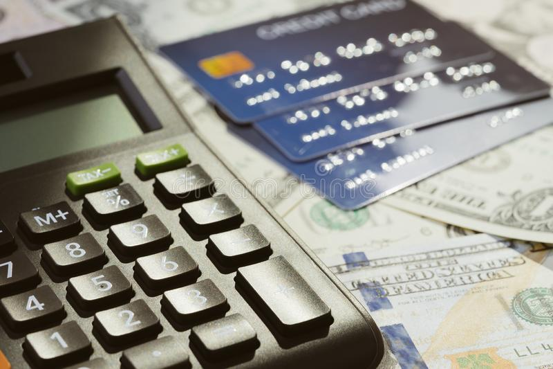 La calculadora negra refleja con la luz del sol por la tarde en la pila de dinero de las tarjetas de crédito y de las cuentas de foto de archivo libre de regalías