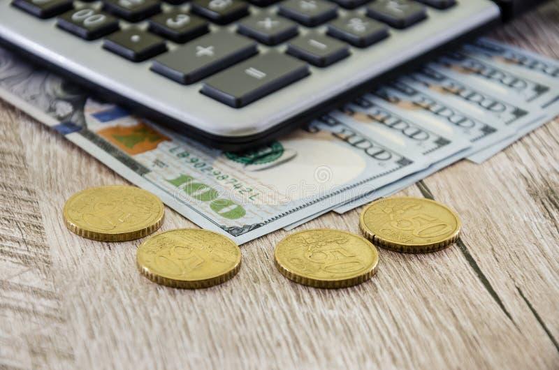 La calculatrice avec des dollars et les pièces de monnaie se ferment  photos stock