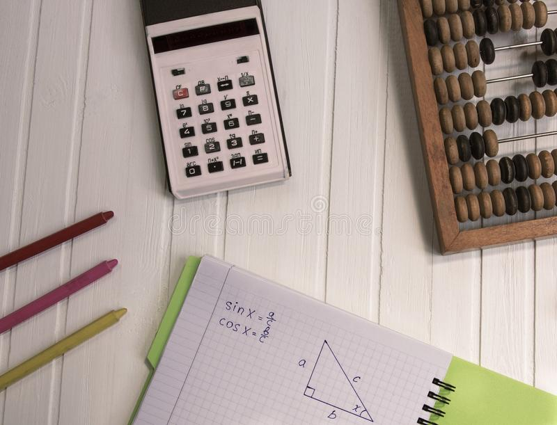 La calculatrice et le bloc-notes se trouvent sur un fond en bois Inventaire d'un écolier ou d'un homme d'affaires photographie stock libre de droits