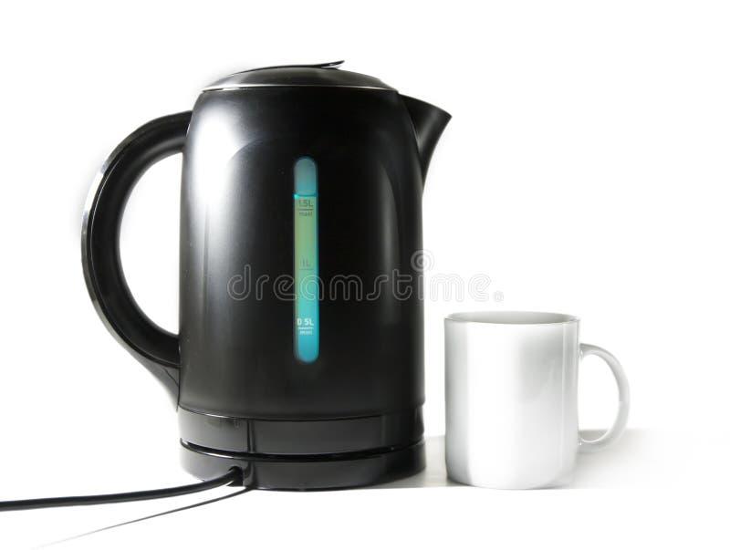 La caldera de té eléctrica y una taza imagen de archivo