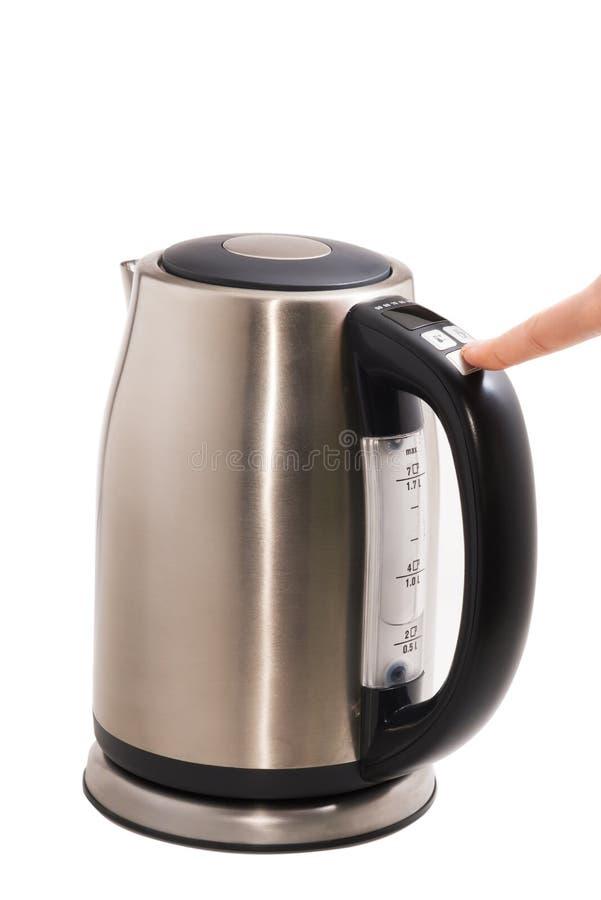 La caldera eléctrica de acero, con el finger presiona el botón foto de archivo