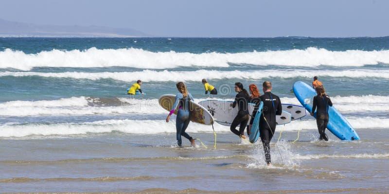 La Caleta, Spagna, 03-14-2019 Gruppo di surfista che cammina nelle onde alla spiaggia di Caleta della La Lanzarote Le Isole Canar immagine stock