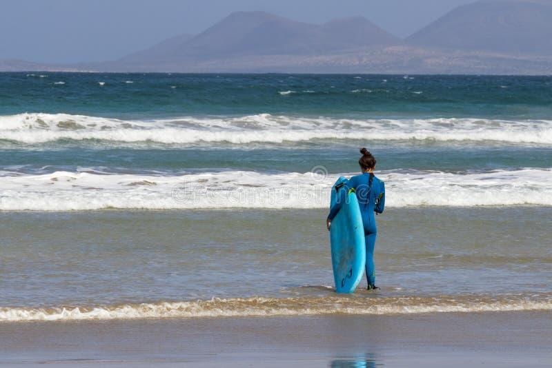 La Caleta, Spagna, ragazza del surfista 03-14-2019 che cammina nelle onde alla spiaggia di Caleta della La Lanzarote fotografia stock