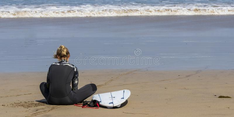 La Caleta, Spagna, ragazza del surfista 03-14-2019 che si siede alla spiaggia di Caleta della La Lanzarote Le Isole Canarie immagine stock libera da diritti
