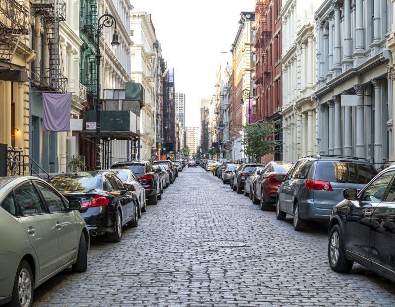 La calle Cobblestone Greene está repleta de edificios y coches en el barrio SoHo de Manhattan, en la ciudad de Nueva York fotos de archivo libres de regalías