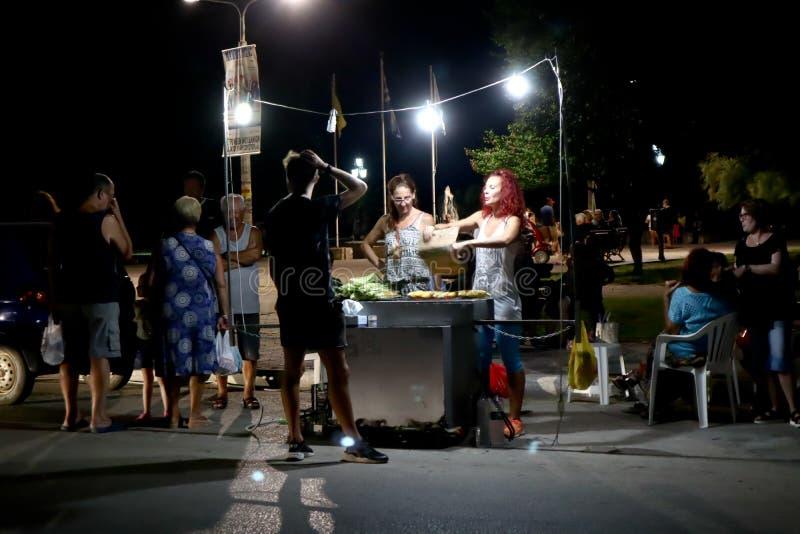 La calle hace una pausa la noche, vendedores que venden maíz asado a la parrilla a los compradores fotos de archivo