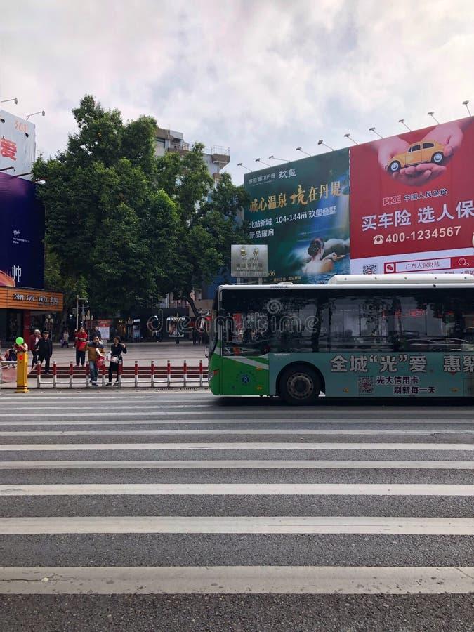 La calle peatonal comercial de la ciudad de Huizhou, el autobús está pasando el paso de cebra al lado de la calle peatonal fotos de archivo libres de regalías