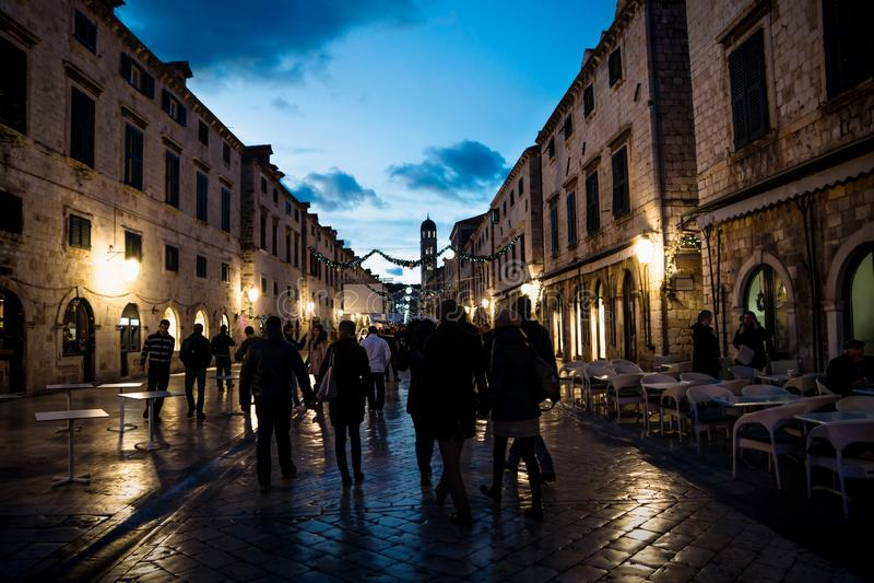 La calle vieja de Stradun en Dubrovnik adornó con las luces y los ornamentos de la Navidad en la noche con la gente que daba une  fotos de archivo libres de regalías