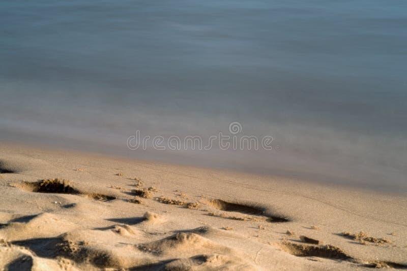 La calma agita en la costa de la arena imagen de archivo libre de regalías
