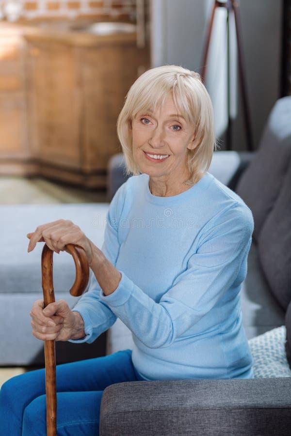 La calma alegre envejeció a la mujer con una sentada y una sonrisa del bastón fotos de archivo