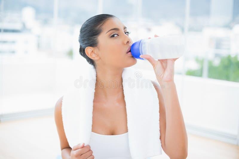 La calma ha tonificato castana con l'asciugamano che beve dalla bottiglia di sport immagine stock