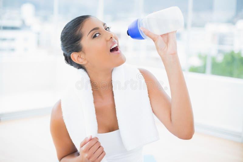 La calma ha tonificato castana con la bottiglia di sport della tenuta dell'asciugamano immagine stock