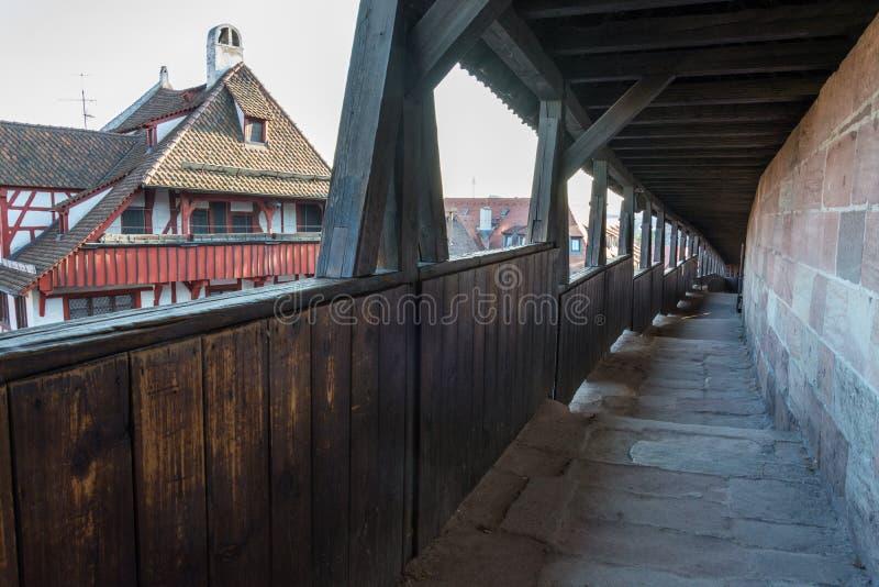La calzada de los guardias con un tejado de madera al lado del castillo de Nure imagen de archivo