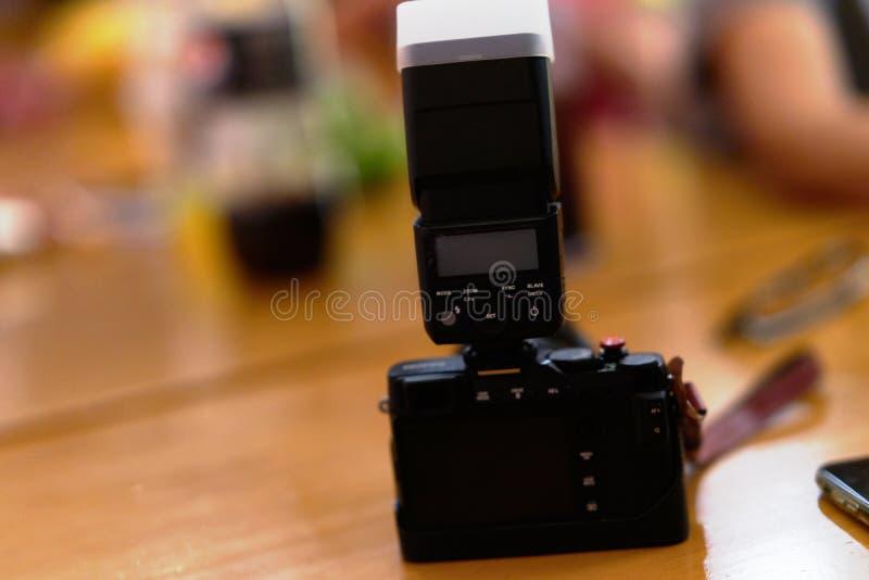 La caméra a attaché la lumière d'instantané avec le couvercle de boîte mou sur le fond de partie de table photographie stock libre de droits