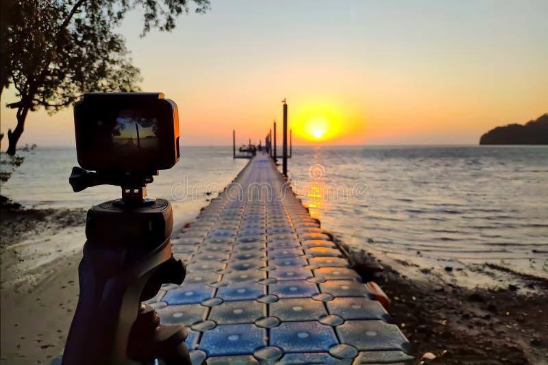 La caméra d'action a monté sur une photographie de trépied le pilier et le lever de soleil sur la plage images stock
