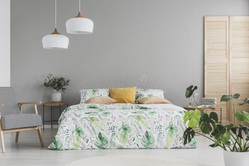 La cama matrimonial con acentos botánicos en las hojas y el melocotón coloreó las almohadas en el dormitorio escandinavo gris, es fotografía de archivo