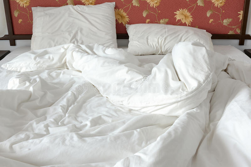 La cama sin hacer/desordenada con un blanco arrugó la manta y dos almohadas sucias en un cuarto de la cama fotos de archivo libres de regalías