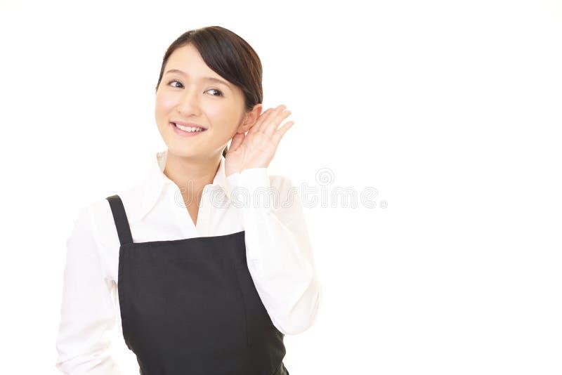 La camarera asiática escucha cuidadosamente fotografía de archivo libre de regalías