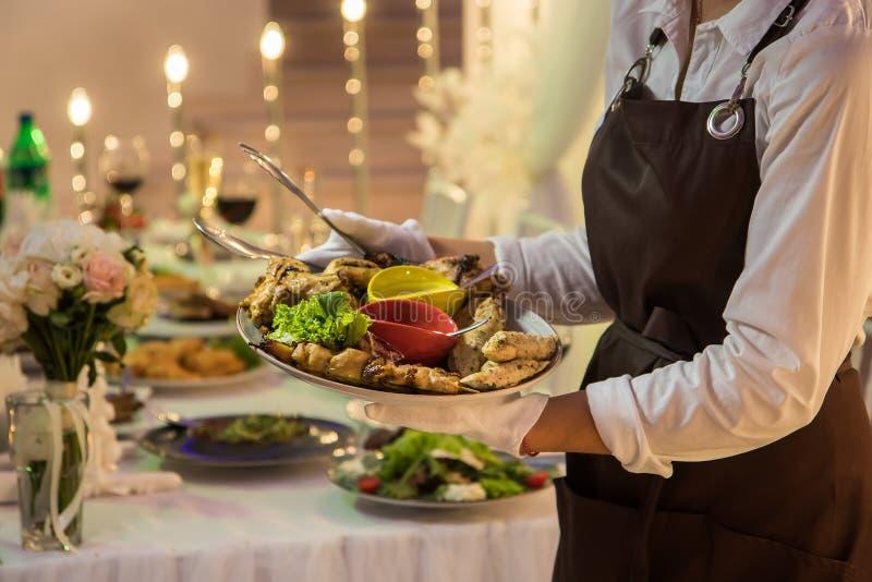 La camarera está sosteniendo un plato con kebabs y rollos del pollo imagen de archivo