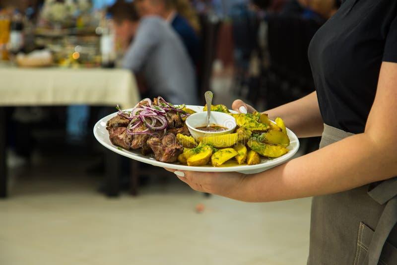 La camarera lleva una placa de patatas y de kebabs sirve una tabla de banquete foto de archivo