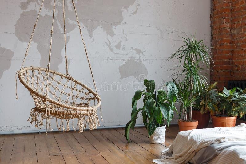 La camera da letto comoda moderna interna con le piante da appartamento verdi e un'oscillazione, sottotetto hanno fornito Idea in fotografia stock