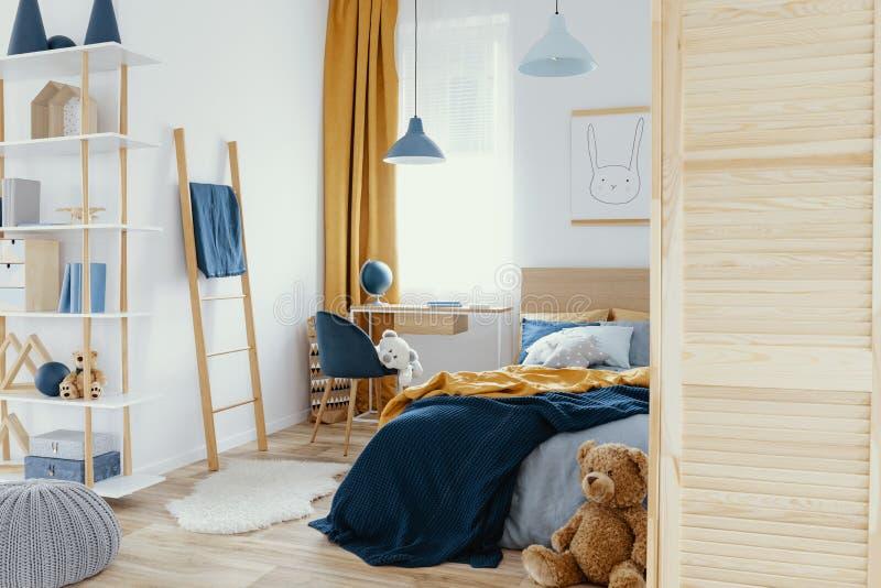 La camera da letto del bambino sudicio con i giocattoli e la foto reale della mobilia di legno fotografia stock libera da diritti