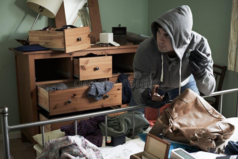 La camera da letto di Stealing Items From dello scassinatore durante la Camera irrompe immagini stock