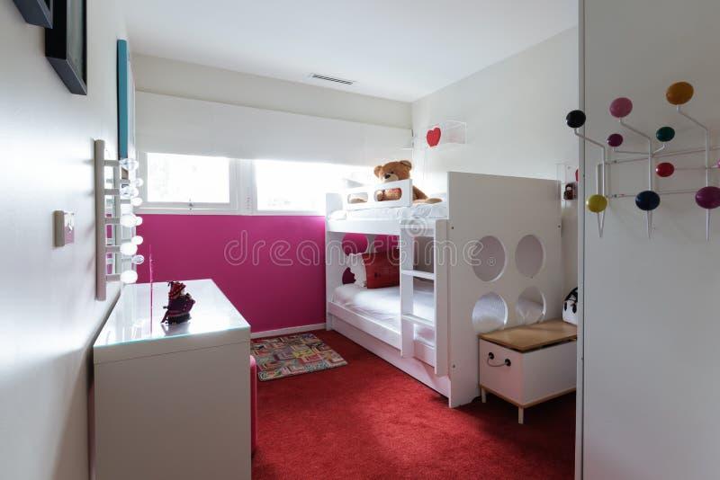 La camera da letto funky dei bambini con tappeto rosso ed il rosa ha dipinto la parete fotografia stock libera da diritti