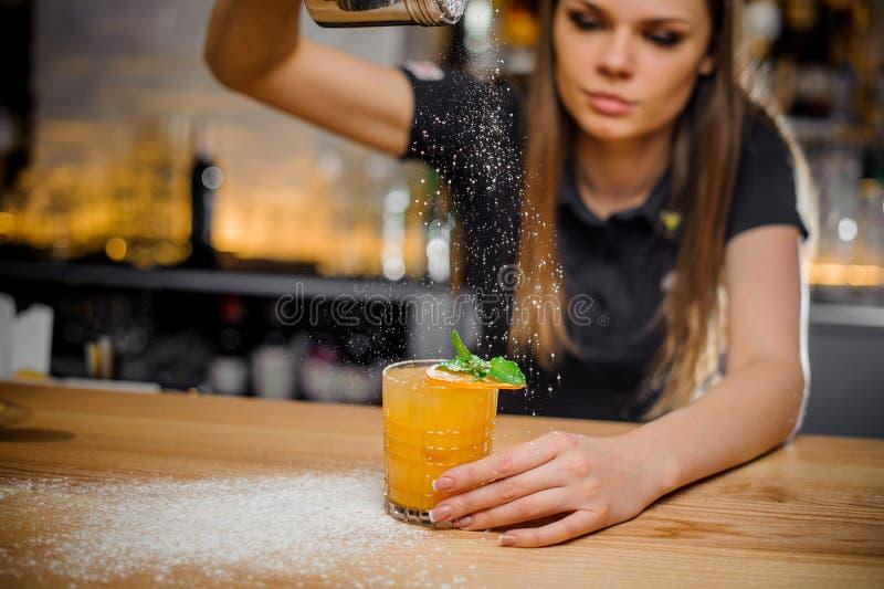 La cameriera al banco finisce la preparazione del cocktail decorata con la menta e l'arancia secca fotografia stock libera da diritti