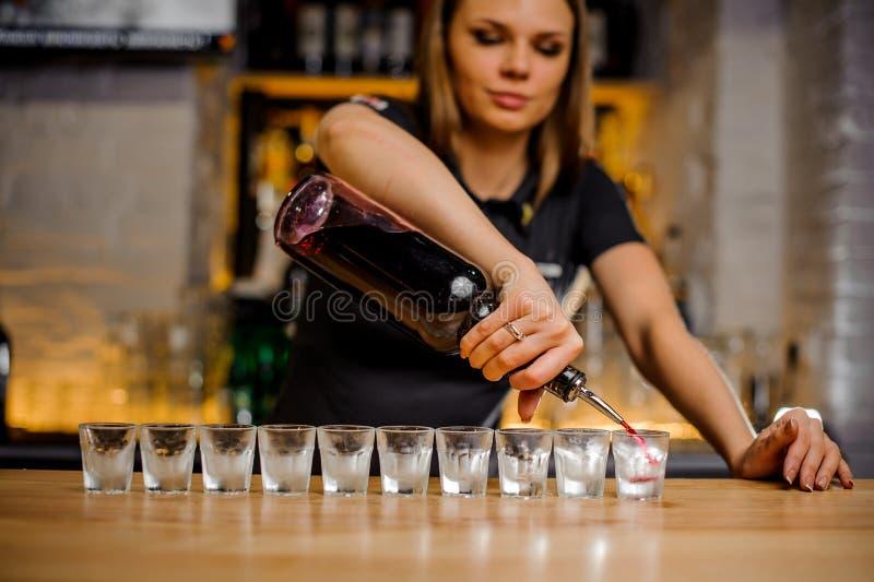 La cameriera al banco versa l'alcool nelle pile di cristallo che sono allineate immagini stock libere da diritti