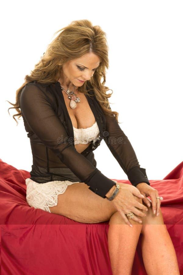 La camicia aperta del reggiseno del pizzo della donna si siede sullo sguardo rosso fotografia stock