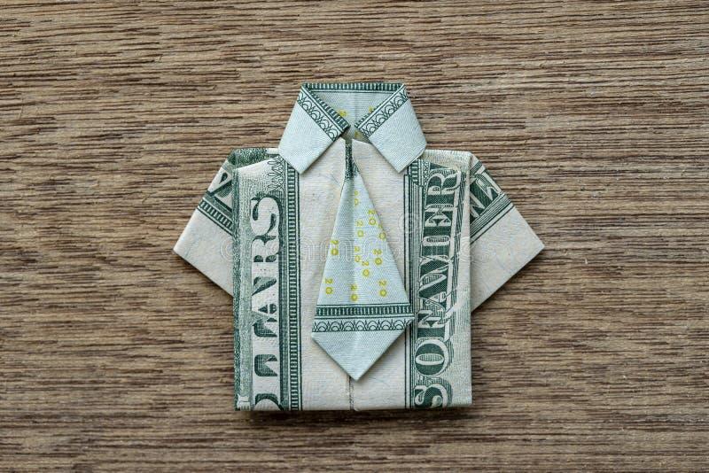 La camicia di origami ha fatto della banconota del dollaro su fondo di legno closeup Maglietta della banconota in dollari fotografia stock libera da diritti