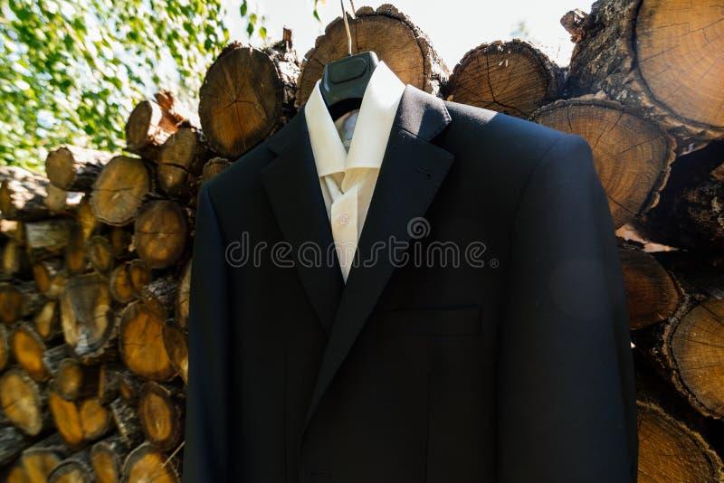 La camicia ed il rivestimento dello sposo appendono su una gruccia per vestiti fotografia stock libera da diritti