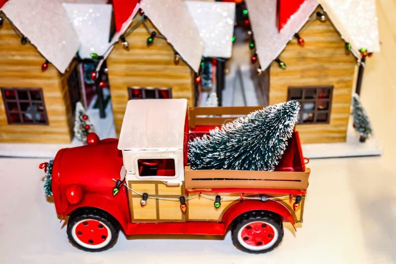 La camioneta pickup roja del juguete del vintage con las luces de la Navidad y el árbol adentro apoyan delante de un pueblo de la imagenes de archivo