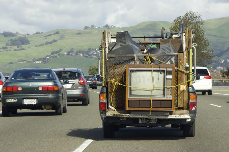 La camioneta pickup vieja transporta las TV viejas imagen de archivo