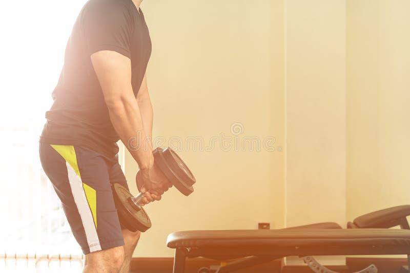La camisa negra de los hombres está levantando pesas de gimnasia fotografía de archivo