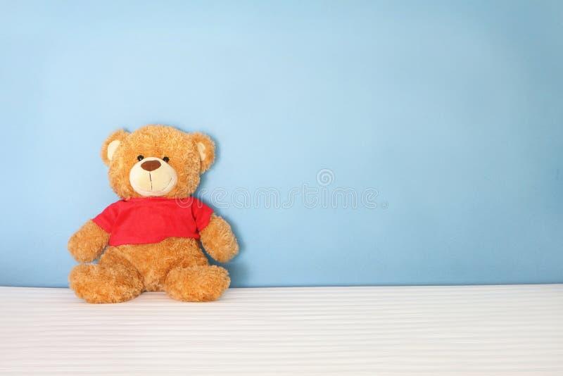 La camisa roja del solo del oso marrón desgaste de la muñeca la sienta en la cama blanca en la pared azul del fondo en la mirada  imagenes de archivo