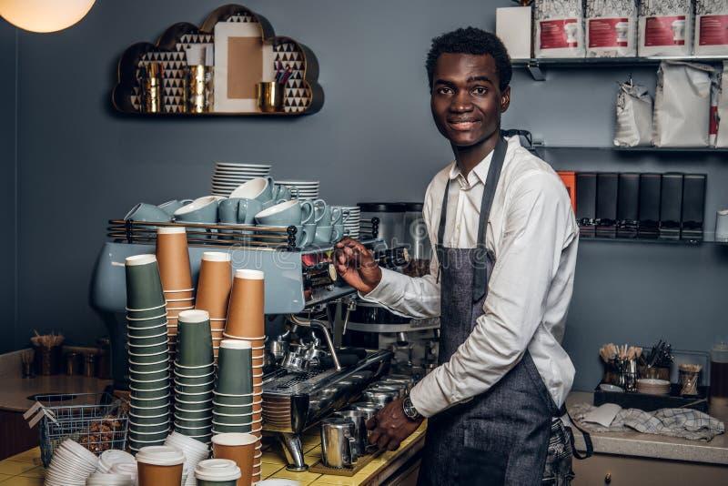 La camisa y el delantal blancos de Barista n hace el café en la máquina del café en una cafetería imagen de archivo libre de regalías