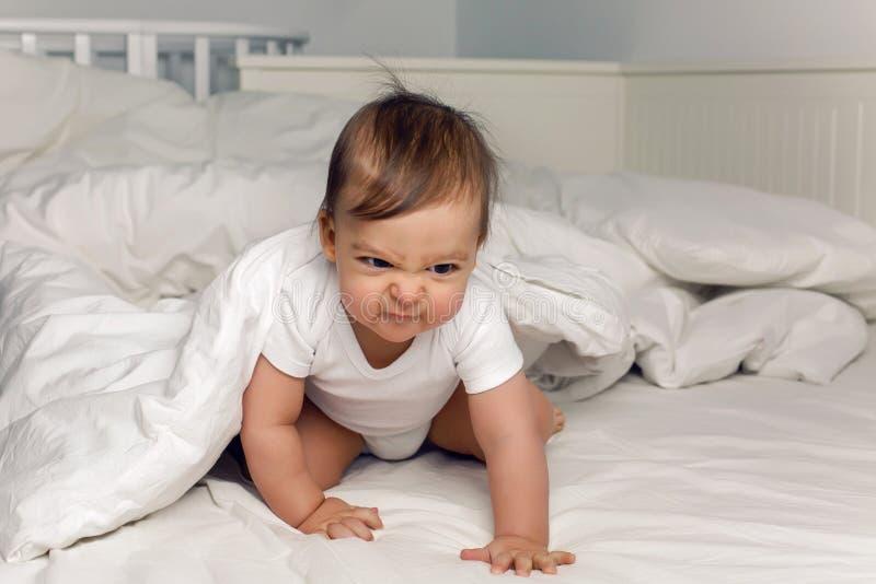 La camiseta del bebé del muchacho miente debajo de una manta foto de archivo