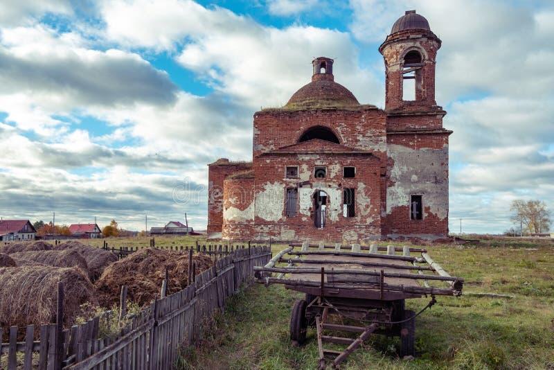 La campagne et le vieux d'église détruits sous le ciel bleu avec des nuages dans le vieux chariot de premier plan pour des chevau image libre de droits