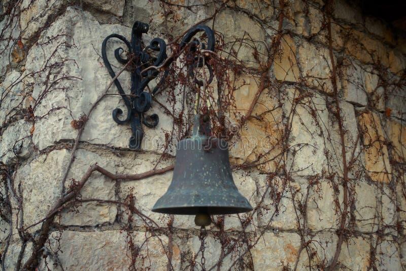 La campana cuelga en la pared vieja en la vid te?ido fotografía de archivo libre de regalías