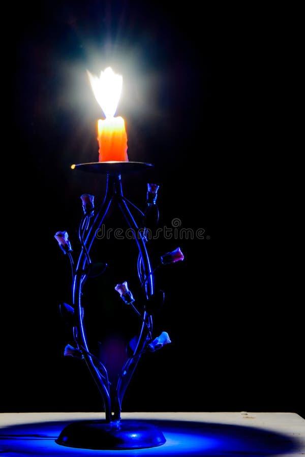 La candela accesa in un vecchio candeliere con fatto a mano è aumentato immagini stock