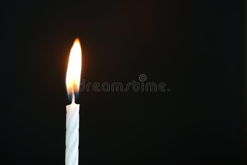 La candela bianca di compleanno contro un fondo scuro immagine stock