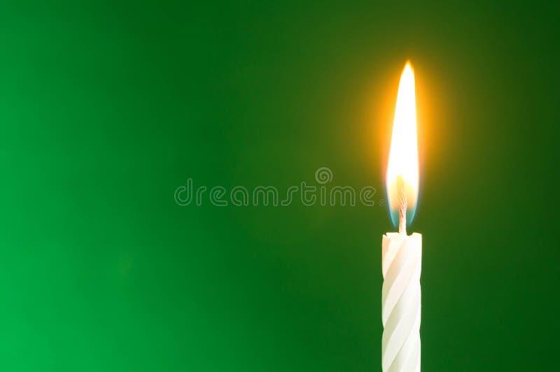 La candela di compleanno su un fondo verde fotografia stock