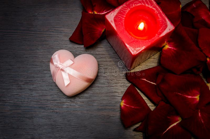 La candela, petalo rosso è aumentato con il contenitore di regalo sulla tavola fotografie stock libere da diritti