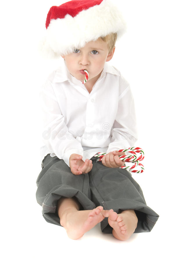 la canne de sucrerie mignonne mange s'user d'enfant en bas âge de Santa de chapeau photos libres de droits