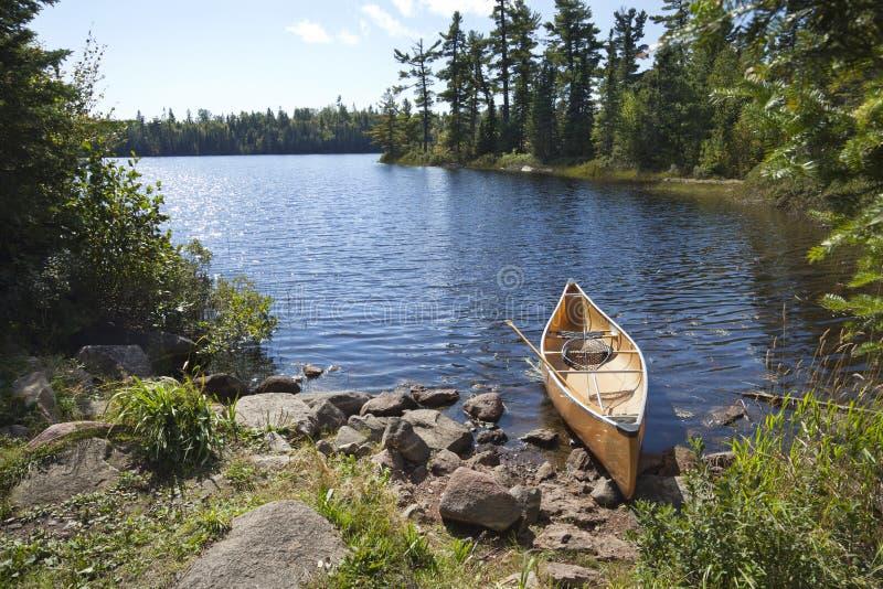 La canoa de un pescador en orilla rocosa en el lago septentrional minnesota fotos de archivo