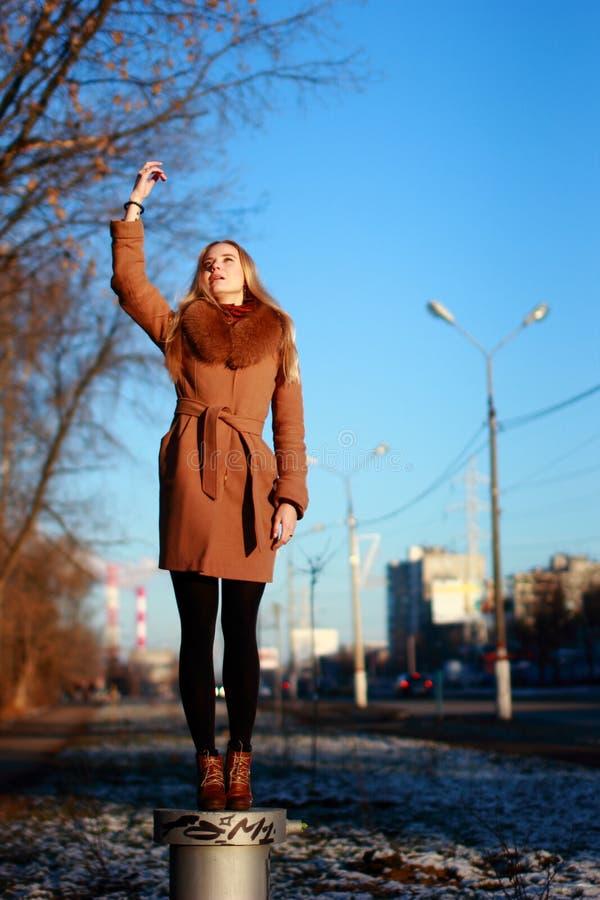 La capa que lleva de la mujer joven se coloca en un soporte, día de invierno frío, Han fotos de archivo libres de regalías