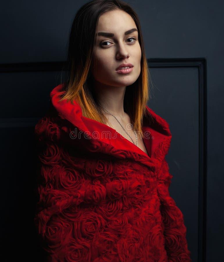 La capa roja de la mujer hermosa con rojo florece rosas en estudio imagen de archivo libre de regalías