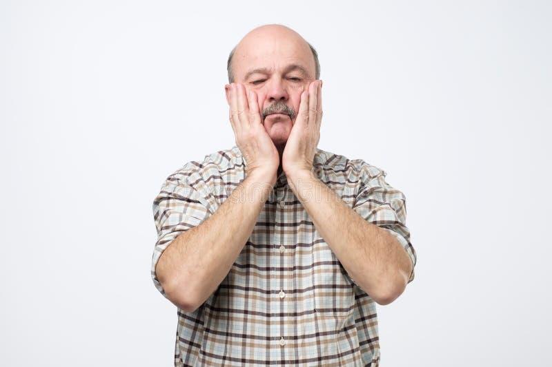 La cara con ambas manos, sensación de la cubierta del hombre mayor subrayó hacia fuera mientras que él suprimió todos los fichero fotografía de archivo